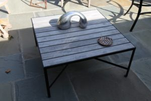 This metal and teak table is the Coffee Table version of John's line of Parsons Tables.