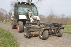 This machine attachment is a type of surface planer, which smooths the surface and takes out any ruts.