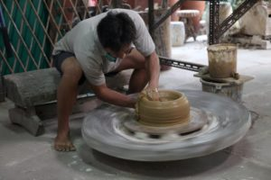 A potter busy at work creating a rather large piece
