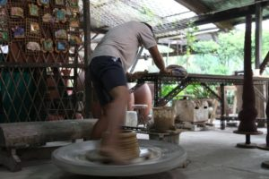 This is very physical work as this potter's wheel is powered by leg strength.