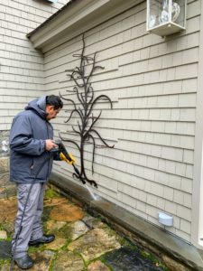 Here, Carlos uses it to clean the stone ledge on my Winter House. Above the ledge is my Metal Tree Wall Decoration from QVC. It is a 71-inch piece featuring 11-rings and pots to hold flowers, small plantings, or fall pumpkins. It can be used indoors and out.