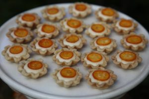 Tartletts filled with pastry creme and topped with candied kumquat slices