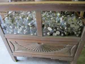 A cabinet filled with glass and silver spice shakers