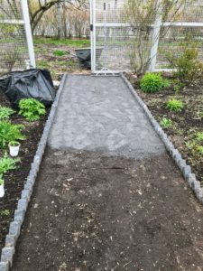 Using a hard rake, Chhiring spreads an even layer of stone dust over the existing soil in the pathways.