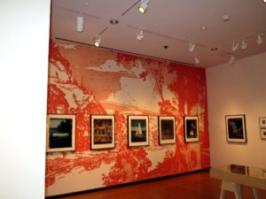 Wegman revisits many of the materials that have shaped our cultural expectations of the outdoors, including Boy Scout Manuals, field guides, nineteenth-century Transcendentalist literature, and postcards.  This wonderful red backdrop is a vinyl blowup of his work.