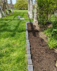 Here's one side all complete. After several hours, this section is edged with bricks. Path edging helps to keep the structure of the path defined and the garden soil well-contained.