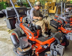 Finally, Pete parks it next to the other mowers. We use big riding zero-turn mowers, stand-on mowers, and for tighter spots near the various buildings, push mowers.