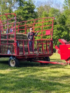 Carlos has one of his crew ride in the trailer to catch the bales as they shoot out of the machine.