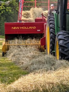 The hay is lifted by tines in the baler's reel and then packed into the bale chamber, which runs the length of one side of the baler.