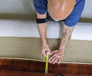 Because the carpet is cut slightly smaller than the space to expose the wood floors, the area between the carpet edges and the walls must be measured several times. This carpet is about four-and-a-half inches from the wall along every side.