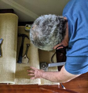 The carpeting on the stairs is also replaced. A carpet knee kicker is used to stretch the carpet. The tool grips the carpet with a set of tines on the head and then pushes it into place.