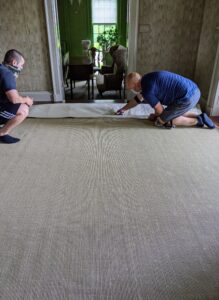In the foyer, the rug is down and the padding is trimmed to fit.