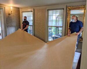 Here, the team adjusts the carpet, so it is completely centered in the room.