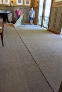Next, the carpet is unrolled and fit into place. Two pieces are needed for this very large room.
