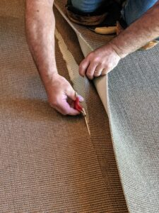 A special pair of carpet scissors is used to trim the overlapping piece before the two pieces are glued together.
