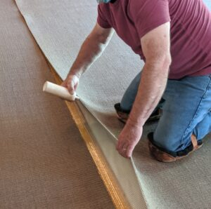 Carpet seam glue is placed on the edges of the carpet so the seams can be sealed.