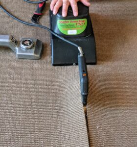 A carpet-seam iron is used to heat the adhesive. Once the pieces are glued together, the Seamer Down Now follows behind to set and cool it.