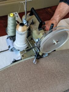 Here, one can see how the edges are serged. The matching colored yarns are placed on spools and the machine quickly wraps the threads over the edges of the carpet.