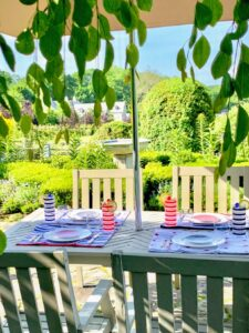 This time of year, I love dining outdoors on my terrace overlooking the paddocks and the lush landscape. Here, we set up four place settings using my Americana appetizer plates in durable and colorful melamine.