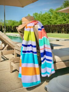 This is my multi-stripe beach towel draped over the corner of one of my chaise lounges by the pool.