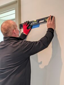 The most time-consuming part of the process is laying out the guidelines for the pieces, so once assembled, the unit would be completely straight and level. Brandon places blue painter's tape on the wall to mark where the pieces should be.