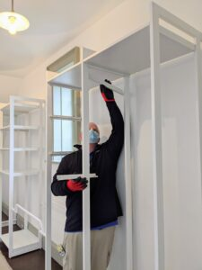 Brandon then starts installing the shelf supports. The shelves can be adjusted to fit specific needs. Here, he is placing them a little more than a foot apart.
