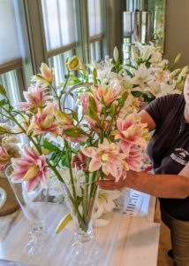 Next, the rose lilies are placed into a vase. While arranging flowers, it is always a good idea to periodically take a step back and look at the display to decide whether any adjustments are needed.