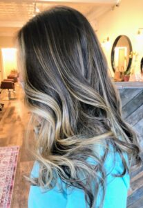 """From the Roots"" provides all hair color services, hair painting, foils, haircutting and styling, and extensions. This client wanted to brighten her blonde hair with some highlights. She got balayage streaks of a lighter shade to add dimension and shine."