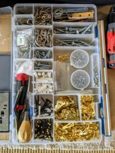 David brings a case filled with all the necessary nails, screws, wall anchors, and hooks.