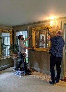 Here, Carlos and David hang the mirror.