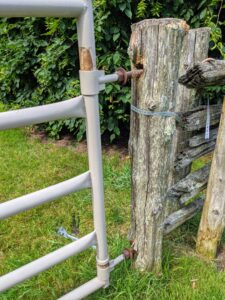 The gate is now separated from the old and deteriorated cedar post upright.