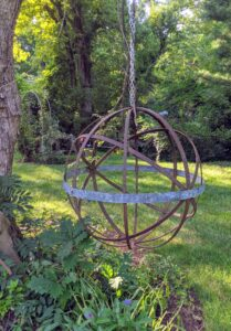 Jim hung this spherical metal garden ornament under a large tree. Laura loved the ornament itself, but apparently not the chain used to hang it.