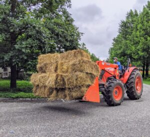 Chhiring loads up our trusted Kubota model M7060HD12 tractor with about a dozen bales of hay - all grown and baled right here at my farm. The bales will help direct the rain water to the appropriate drains.