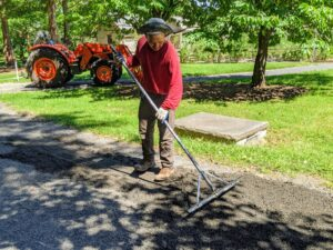 Then Chhiring follows with a rake to spread and blend the gravel into the surrounding areas.