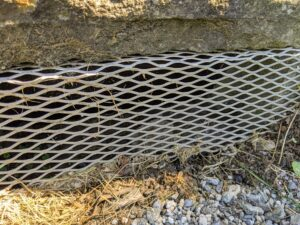 Grated drain coverings are on the sides. The purpose of a catch basin is to collect debris, leaves, and other objects that are moved by flowing water. Keeping these basins clean prevents water-logging and ponding in the surrounding areas.