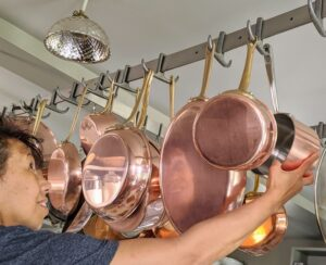 And lastly, after cleaning and drying, Elvira carefully hangs the pots and pans back on the rack.