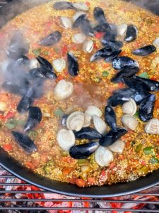 "Here is a closer look at the cooking paella. Paella means ""frying pan"" in Valencian, Valencia's regional language. The paella is mixed until most of the liquid is absorbed and the rice is al dente."