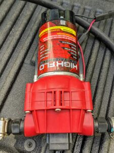 The hose and tank are also connected to a pump and 12-volt battery.