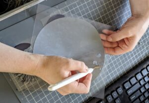 Shqipe works on a self-healing cutting mat to protect the desk surface. This process takes several minutes depending on how much needs to be cut-out.