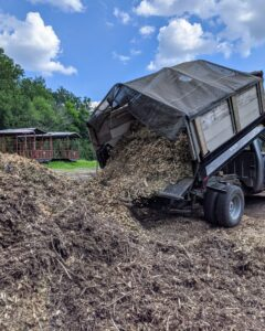 The crew unloads the wood chips into its own pile - the first pile as one enters the compost yard.