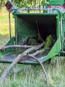 Other pieces are placed into our wood chipper - a machine with sharp moveable blades that can cut wood up into small pieces. Branches, as well as underbrush, can all run through the chipper – everything is returned to the earth, organically and efficiently.