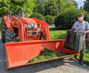 Here's Fernando unloading a bag of grass clippings into the bucket of our Kubota M7060HD12 tractor. This tractor is used around the farm every single day.