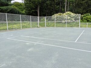 My tennis court is nestled in a far corner of my Bedford farm. The court surface is made with green clay, or HAR-TRU, and should be replaced before the beginning of each season, and maintained periodically through the season, depending on how much the court is used.