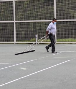 The drag broom is used to even out the new layer of HAR-TRU across the entire surface of the court.