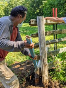 This takes some time to do. They are all wedged in pretty tightly. Pete uses a crowbar to help loosen the post.