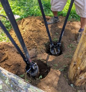Next, Pete and Fernando begin digging new holes by hand using post hole diggers, a hand tool used to manually dig deep and narrow holes in order to install fence posts. A post hole digger is also known as a clamshell digger, because of its resemblance to the seaside shell.