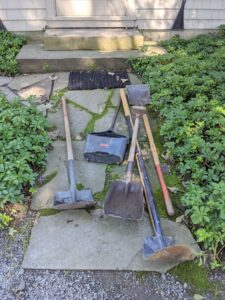 Chhiring uses several different sized shovels to clean the catch basins.