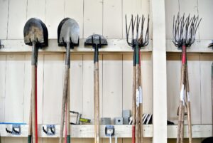 Tools are hung so that they are easy to find. Dirt is rinsed off outdoors before they are put away.