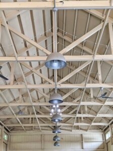 The Equipment Barn is well lit with natural light through windows and these big overhead lamps. I use very utilitarian lighting and fans where I can on the farm.