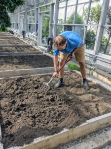Next, using a garden fork, Brian tills the top six to eight inches of compacted soil.